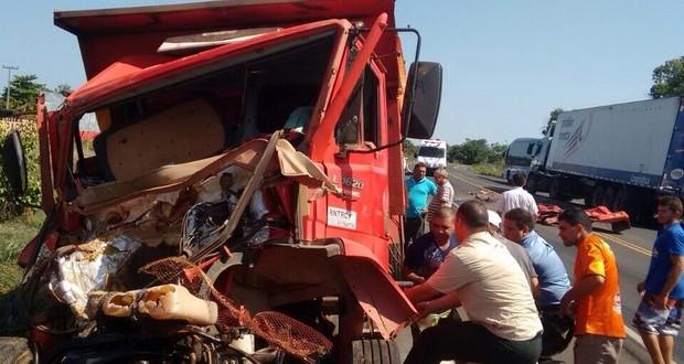 Caçamba bate de frente com carreta e motorista fica preso às ferragens