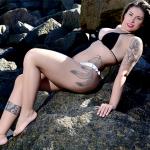 Gari gata posa de biquíni em praia e mostra tatuagem enorme; veja fotos