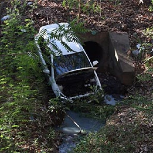 Motorista tenta trocar CD, perde controle e carro cai em barranco