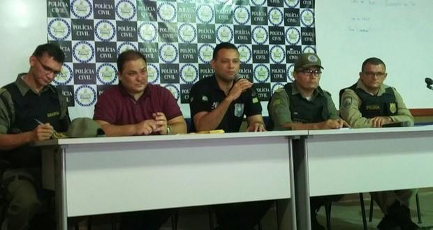 Delegado geral, Riedel Batista, no centro da mesa, fala sobre a operação