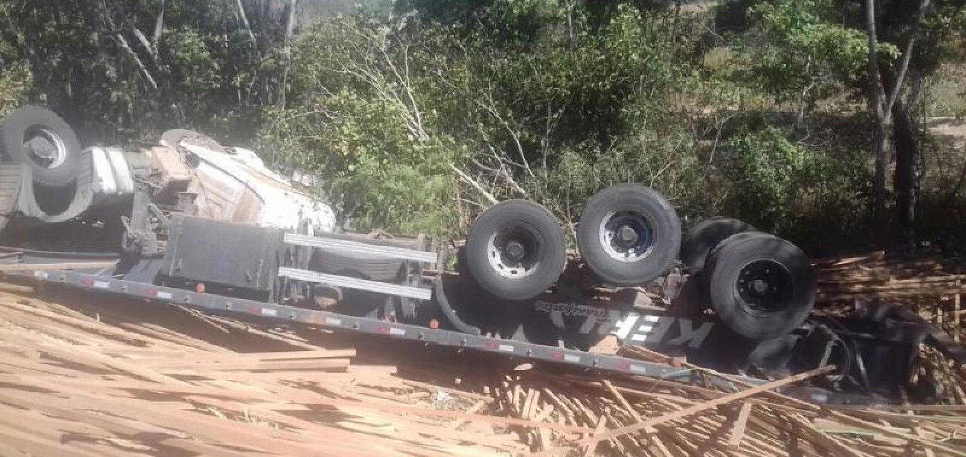 Carreta carregada com madeira tomba e parte da carga é saqueada
