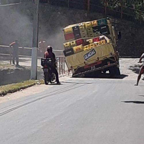 Estrutura cede e caminhão fica com roda presa em ponte sobre o sangradouro